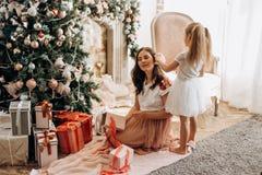 Den lyckliga unga modern och hennes lilla dotter i trevlig klänning sitter nära det nya årets träd och öppna nytt års gåvo arkivbild