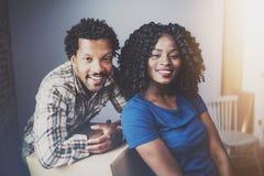 Den lyckliga unga parflyttningen för svart afrikan boxas in i den nya lägenheten tillsammans och danande per härligt liv gladlynt arkivfoto