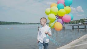 Den lyckliga unga pojken går med färgglade ballonger på kusten av sjön 4K stock video
