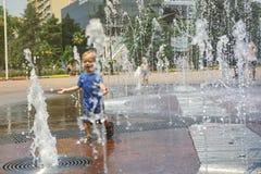 Den lyckliga unga pojken har gyckel som spelar i vattenspringbrunnar arkivfoton