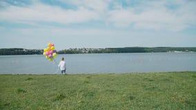 Den lyckliga unga pojken står med färgglade ballonger på kusten av sjön 4K stock video