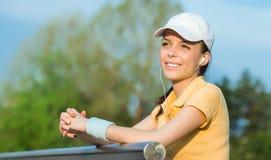 Den lyckliga unga sportkvinnan hör musik, Royaltyfri Bild