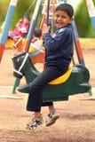 Den lyckliga unga stiliga pojken (unge) som spelar på gunga, ställer in i en parkera Arkivbilder