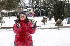Den lyckliga unga turkiska kvinnan spelar med en snö som är utomhus- i en vinterdag royaltyfri foto
