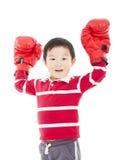 Den lyckliga unga ungen med boxninghandsken, i att segra, poserar Royaltyfri Fotografi