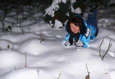 Den lyckliga unga vita kvinnan ligger i en snöig snödriva och leenden, glade sinnesrörelser på flickans framsida royaltyfri foto