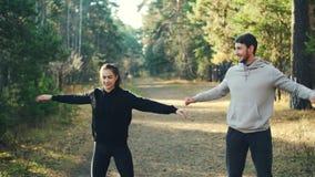 Den lyckliga den ungdommannen och kvinnan gör sportar parkerar in att öva utomhus att le, samtal och att skratta ha gyckel Barn arkivfilmer