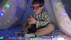 Den lyckliga ungen ser in i smartphonesammanträde i vigvamdekor med en hemmastadd girland arkivfilmer