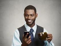 Den lyckliga utövande hållande mobilen, ilar telefonen som dricker kaffe royaltyfri fotografi