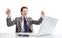 Den lyckliga utövande mannen som ser en bärbar datordator med armar, lyftte I Arkivbilder