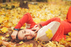 Den lyckliga vila flickaståenden som ligger i höstlönnlöv parkerar in, stängda ögon, iklädd modetröja Arkivbild
