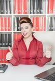 Den lyckliga visningen för affärskvinna tummar upp och blinkningen arkivfoton