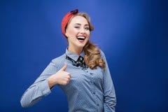 Den lyckliga visningen för ung kvinna för leende tummar upp Arkivbild