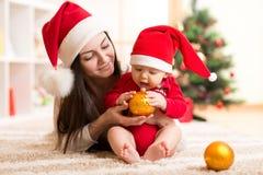 Den lyckligt modern och förtjusande behandla som ett barn i dräkt av jultomten Fotografering för Bildbyråer