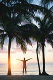 Den lycksaliga konditionkvinnan som tycker om avslappnande solnedgång för strand gömma i handflatan under Fotografering för Bildbyråer