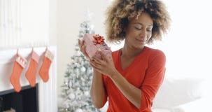 Den lycksaliga lyckliga unga kvinnan rymmer en julgåva Arkivfoton