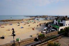 Den Lyme Regis stranden och hamnen Dorset UK seglar utmed kusten i solskenet för sen sommar Fotografering för Bildbyråer