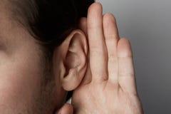 Den lyssnande mannen rymmer hans hand nära hans öra över grå bakgrund closeup royaltyfri bild