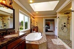 Den lyxiga badruminre med badet badar och den glass dörrduschen Arkivbild