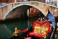 Den lyxiga gondolen parkerade och järnbron, Venedig, i Italien, Europa arkivfoto