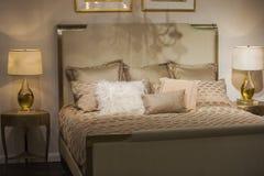 Den lyxiga inre planlade sovrummet med antika härliga nattduksbord och lampor på dem, i guld- färger, med guld- kuddar royaltyfri foto