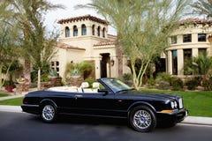 Den lyxiga konvertibla bilen parkerade framme av ett herrgårdhus Arkivbild