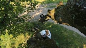 Den lyxiga lyckliga blonda bruden och den stilfulla brudgummen möter i den gröna sommarskogen, mjukt ögonblick Top beskådar lager videofilmer