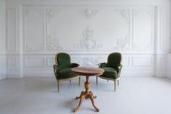 Den lyxiga rena ljusa vita inre med gamla antika stolar för en tappninggräsplan över väggen planlägger basreliefstuckaturstöpning Royaltyfri Fotografi