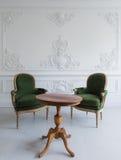 Den lyxiga rena ljusa vita inre med gamla antika stolar för en tappninggräsplan över väggen planlägger roccocoen el för basrelief Arkivbild