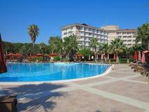 Den lyxiga simbassängen och gömma i handflatan i det tropiska hotellet Arkivbild