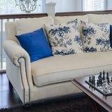 Den lyxiga soffan med blått kudde på brun matta i vardagsrum Arkivfoto