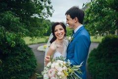 Den lyxiga stilfulla unga bruden och brudgummen på bakgrunden fjädrar su royaltyfri foto