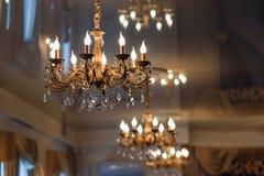 Den lyxiga tappningljuskronan som hänger på taket med att glöda, tänder Royaltyfri Foto