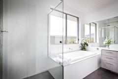 Den lyxiga toaletten med vita väggar och badet badar Royaltyfri Fotografi