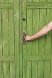 Den mänskliga handen öppnar en stängd dörrtappning arkivbild