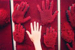 Den mänskliga handen gömma i handflatan kontra handtryck arkivfoto