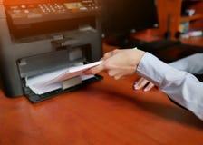 Den mänskliga handen lägger tillbaka papperet till skrivarmagasinet arkivbilder