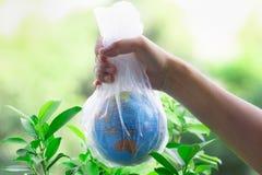 Den mänskliga handen rymmer planetjorden i en plastpåse royaltyfri bild
