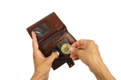 Den mänskliga handen tar eller sätter det guld- myntet av bitcoin från brun leath Royaltyfri Foto