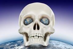Den mänskliga skallen på en bakgrund av planetjorden. Royaltyfria Bilder