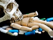 Den mänskliga skallen på trädockan som är mångfärgad av droger och kapsel, är på den svarta bakgrunden close upp Vi är mot droger arkivfoto