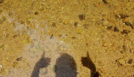 Den mänskliga skuggaelevatorhanden och två tummar upp i vatten Royaltyfria Foton