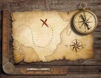 Den mässingsantika nautiska kompasset med gammalt kartlägger Arkivfoto