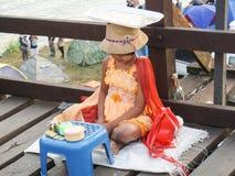 Den måndag ungen sätter en platta på hennes huvud som är kulturen av den måndag groen Arkivfoton