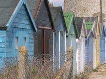 Den mång- kulöra stranden förlägga i barack längs den engelska kusten Arkivfoto