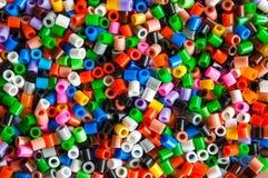 Den mångfärgade plast- hamaen pryder med pärlor leksaken för ungar Fotografering för Bildbyråer