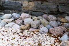 Den mångfärgade rundan stenar framme av en tegelstenvägg Arkivbild