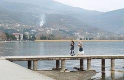 Den mångkulturella familjen går på pir av Ohrid sjön Royaltyfria Bilder