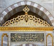Den mönstrade bågen och de calligraphic inskrifterna på väggen av Royaltyfri Fotografi