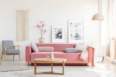 Den mönstrade fåtöljen och rosa färger uttrycker i feministisk lägenhetinre arkivfoto
